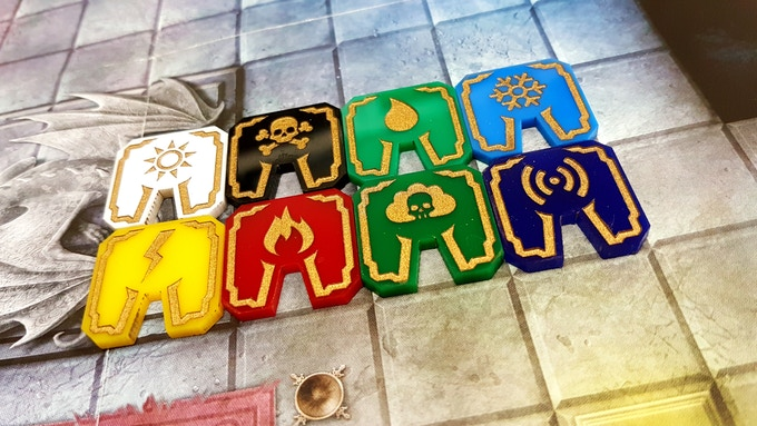 A set of eight (8) Magitags, with classic fantasy frame and custom iconography for (top row, left to right) Radiant, Necrotic, Acid, Cold and (bottom row, left to right) Electricity, Fire, Poison and Thunder effects, inlaid with gold paint.