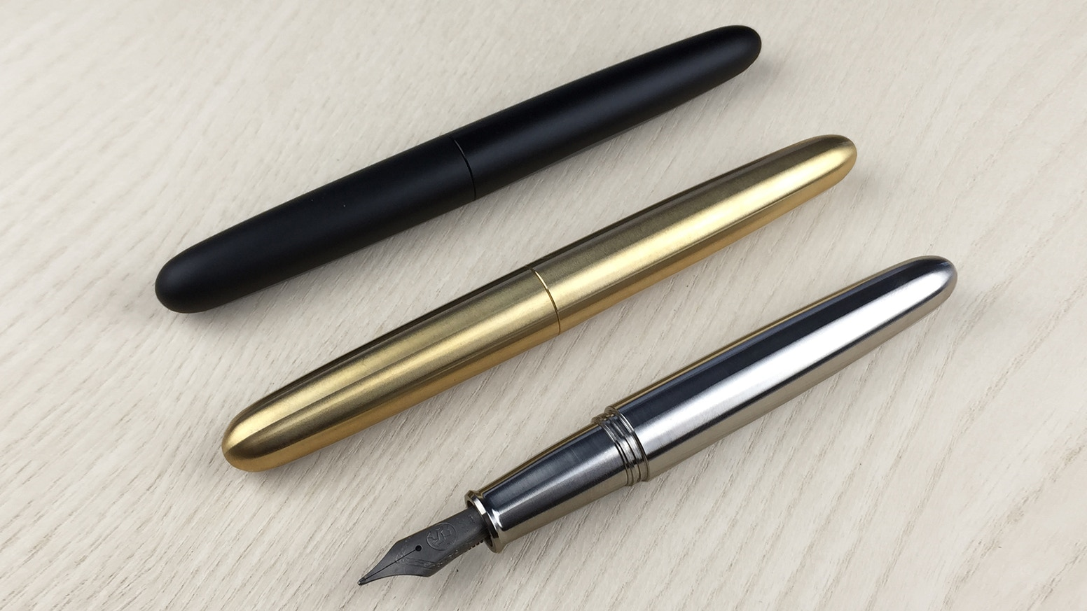 Sleek, minimal, and elegant fountain pen in solid titanium, brass, and black aluminum. Designed to be enjoyed for generations.