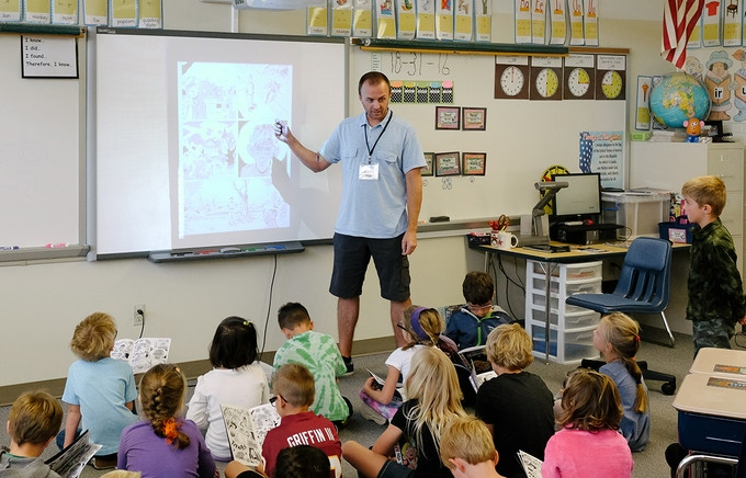 James talking to a 1st grade class about making comics .