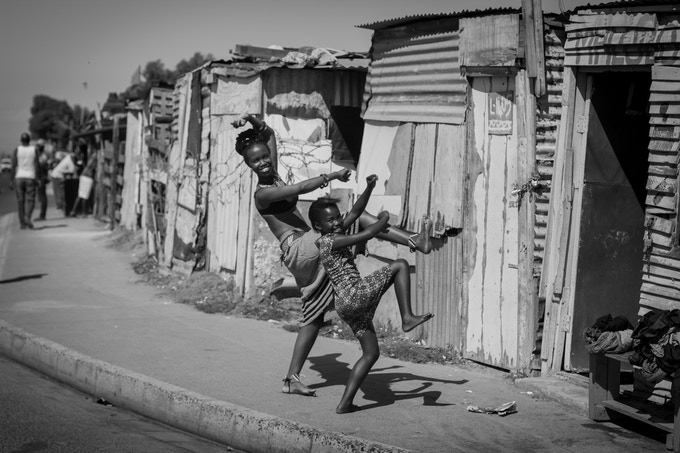 Aphiwe dances amongst the shacks. Young children playing in the streets take notice and join in...
