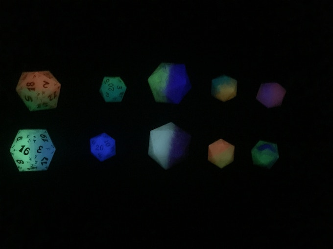 A random assortment of full colored dice in the dark