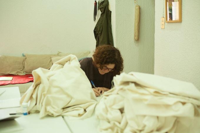 Madda making notes between piles of fabric / Madda haciendo anotaciones entre montones de tela