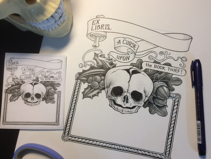 A comparison of a bookplate (left), the original artwork (right) and a skull and some scissors. A pen, too.