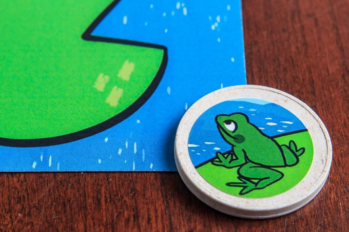Make contact with the target Lily Pad Card and take the Bug Score Card. If the frog disc lands directly on the target Lily Pad flip the Bug Score Card to the flower side for DOUBLE points!