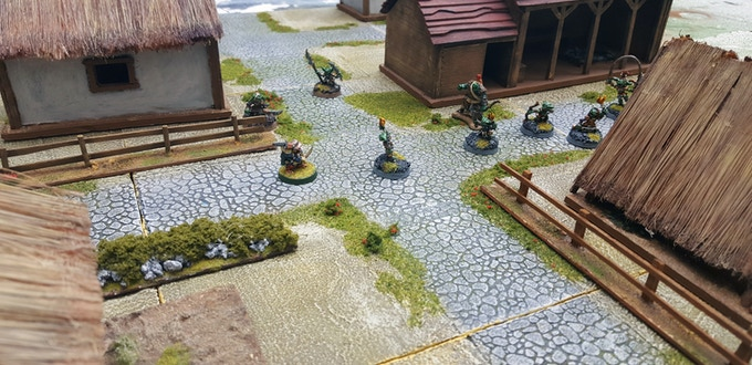 The exact same board, now populated with buildings, miniatures and scenery to create a fantasy Village with some Goblin Raiders (Buildings and models included only for demonstration purposes; not part of the sets)
