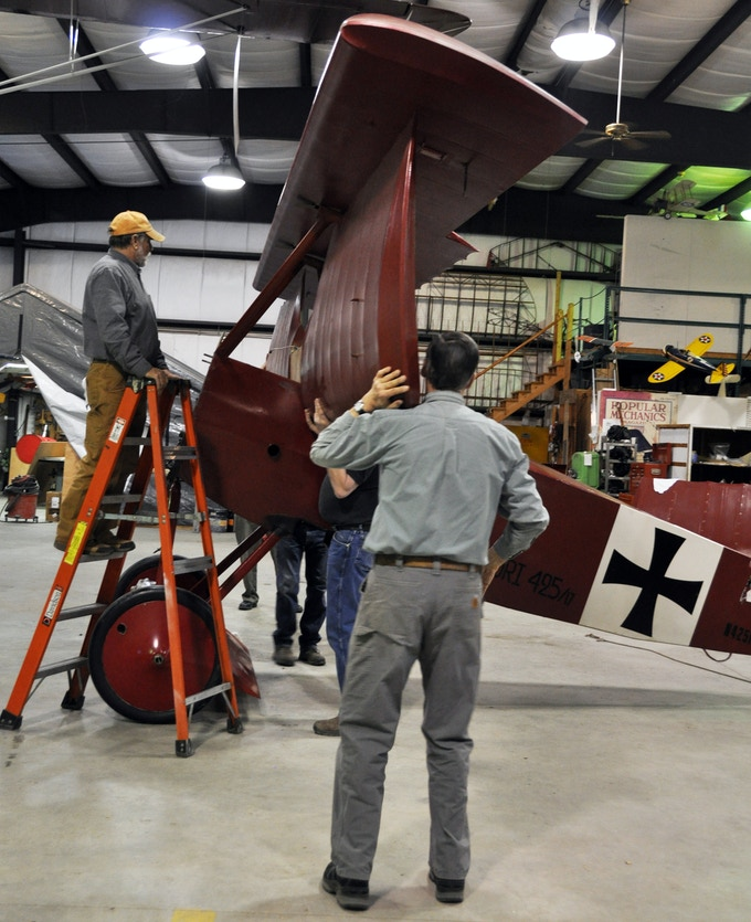 Volunteers help Aircraft Conservator Bob Bailey take a closer look at the Fokker Dr.I.
