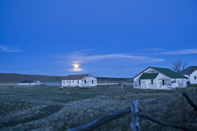 A full moon rises over Reinecker Ridge with the Cook's House and Bunk House in the foreground. Photo by Dan Mitchell