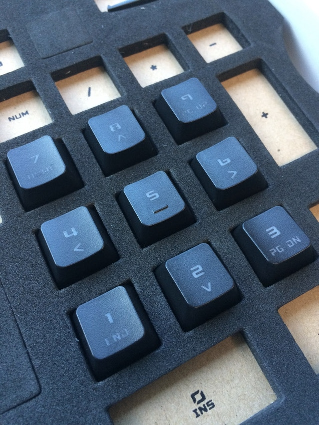 An upclose view of the keycap foam template with a few keys fitting smoothly within each hole.