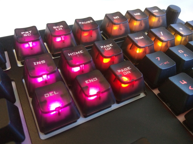 Translucent black keycaps with inscriptions are featured above. The keyboard is NOT the 5Q.