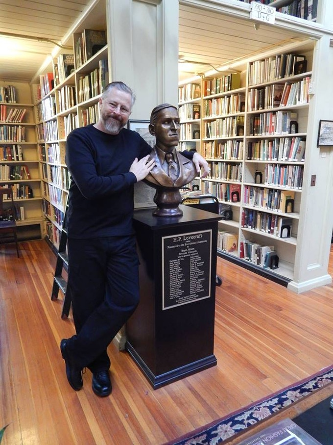Bryan Moore and his bust of H.P. Lovecraft at the Providence Athenaeum Library in Rhode Island.