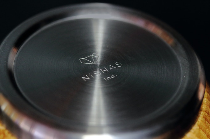 The bottom of the tumbler with the Nisnas logo in stainless