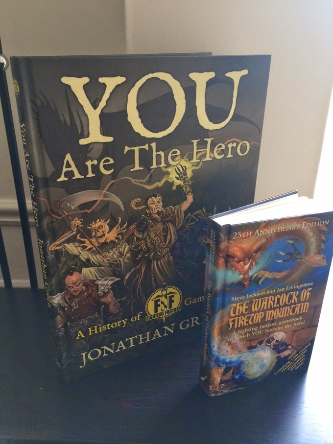 YOU ARE THE HERO (Part 1) next to the 25th anniversary hardback edition of The Warlock of Firetop Mountain.