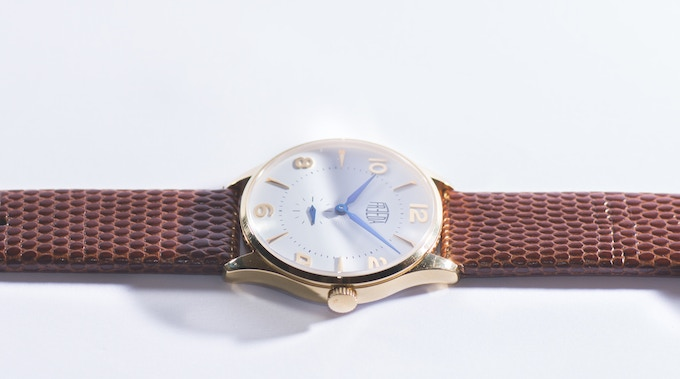 Plano gold/white featuring blue hands and a brown lizard strap