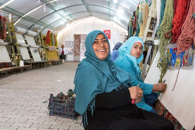 Neriman weaves with her daughter after school in one of our six workshop tents in Adiyaman refugee camp