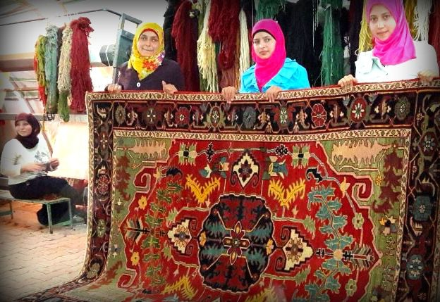 These women proudly display this rug they crafted for an Embassy in Turkey