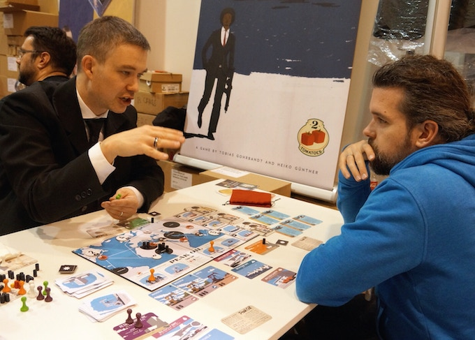 Co-author Tobias explaining to a tester why he always wins at Peak Oil (Essen Spiel 2016)