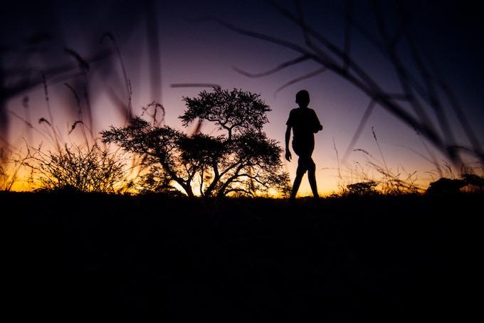 A young Bushman wanders home.