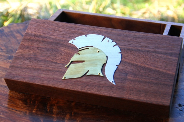 Mixed metal Spartan symbol on Walnut.