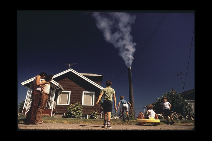 Children Play in Yard of Ruston Home, While Tacoma Smelter Stack Showers Area with Arsenic and Lead Residue. Photographer: Gene Daniels