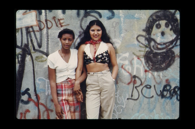 Two Latin Girls Pose in Front of a Wall of Graffiti in Lynch Park in Brooklyn, New York City. Photographer: Danny Lyon