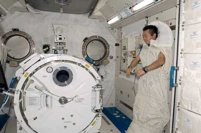 A sleeping astronaut demonstrates truly neutral ergonomic posture, with arms resting around 130-degrees