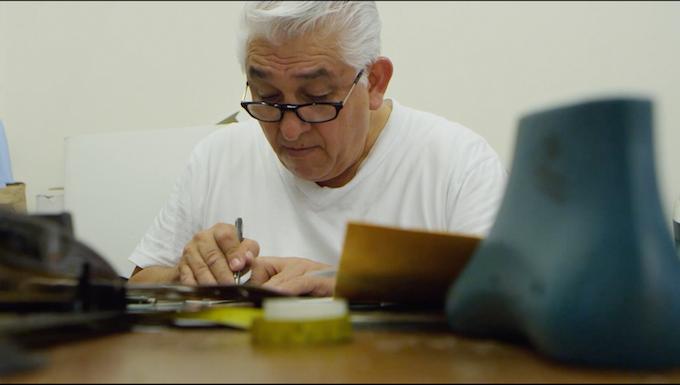 Don Carlos carefully cutting patterns.