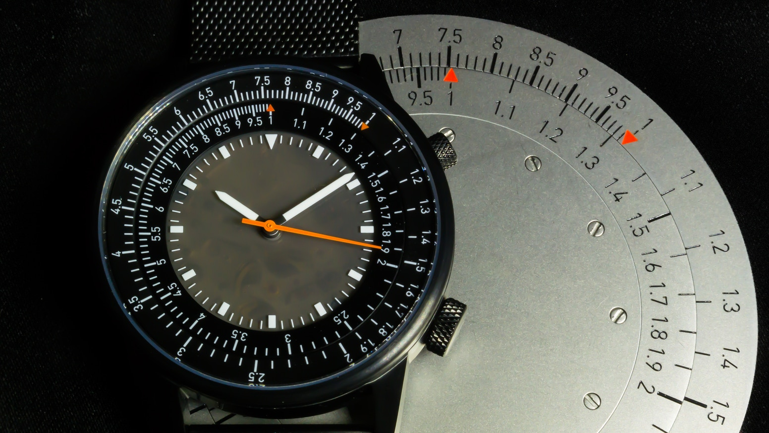 A mechanical watch with an integrated slide rule. Includes a separate circular steel slide rule.