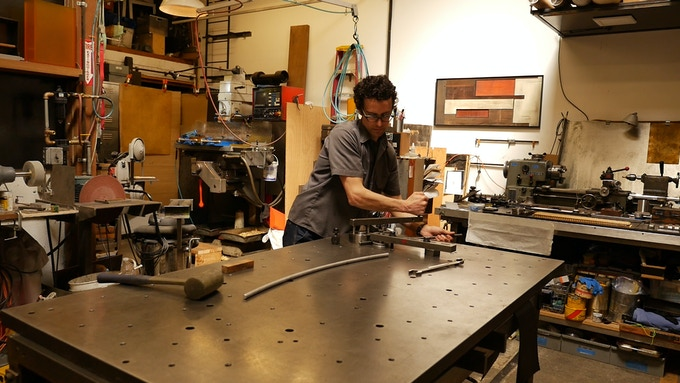 Brian testing different metal types for creating the rods used to hold the costume material in the air