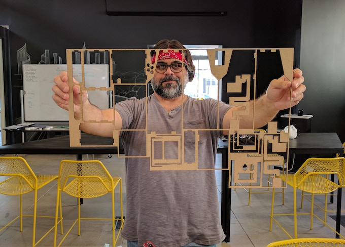 Mike holding laser cut MDF remnants from cutting out the V.5 MDF prototype