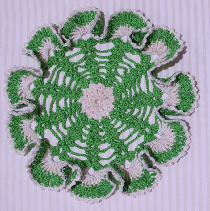 Green and white doily crocheted by Sandi Horton.