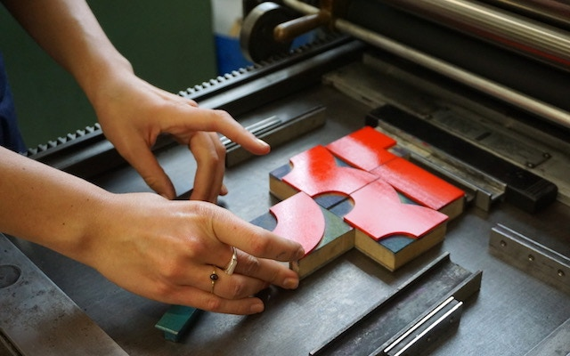 A studio member printing from lasercut ornaments on one of our six letterpress proofing presses
