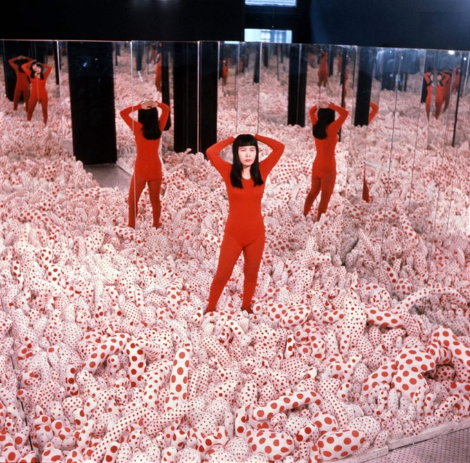 Yayoi Kusama standing in one of her Infinity Rooms