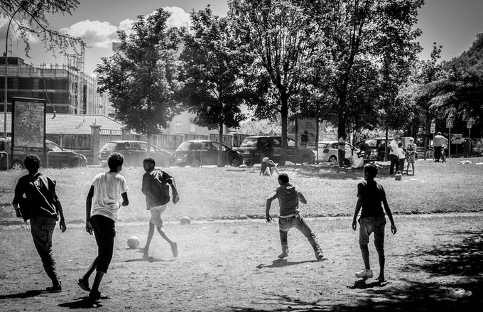 Migrants play football in Como's railway station park (Photo by Emanuele Amighetti. A small printout of this photo is included in the limited edition of the book)