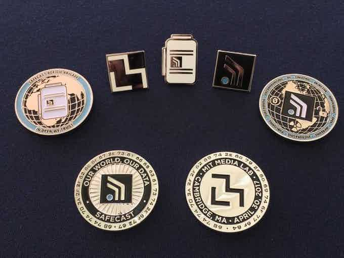 Some previous Safecast Challenge Coins and pins