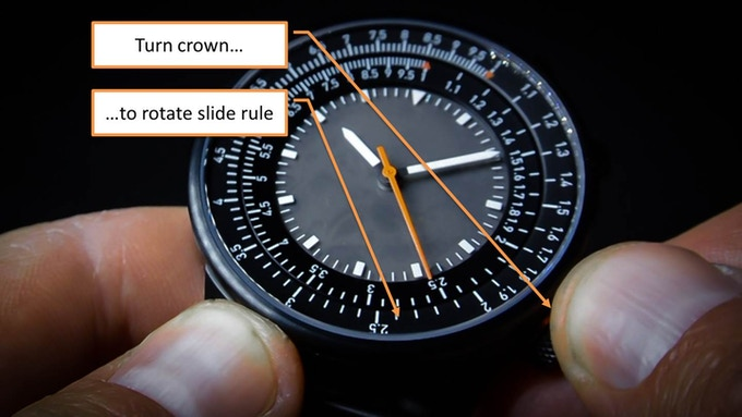 The lower crown controls the slide rule under the crystal