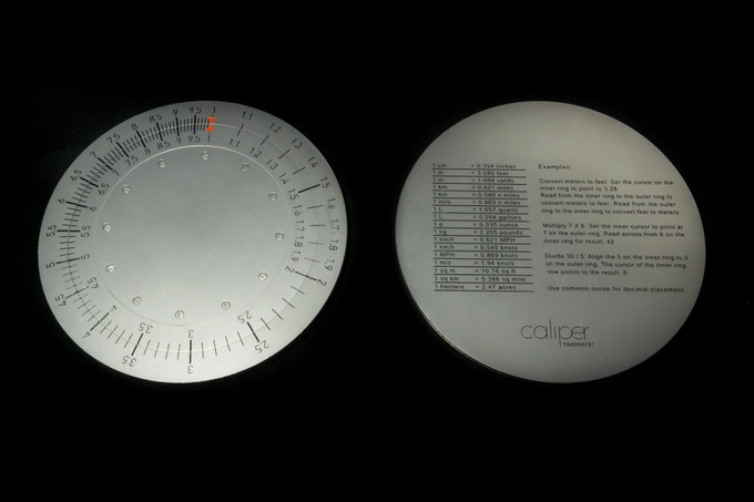 Steel circular slide rule with conversion factors on reverse side