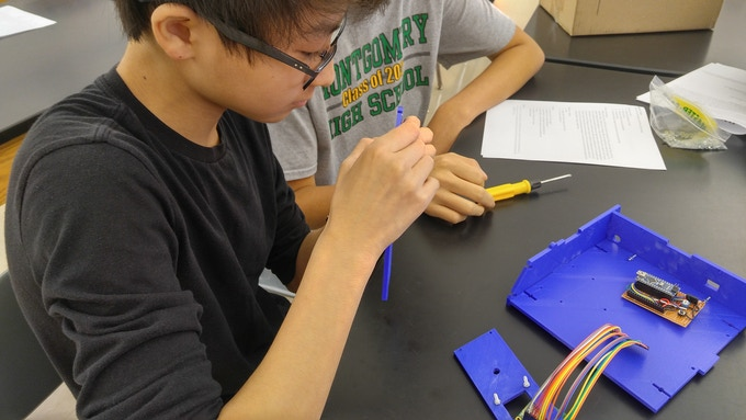 Wilson Wu (high school sophomore) works on assembling a Polyfuge kit with other students.
