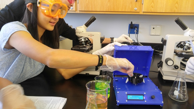 Michelle Qing (high school STEM student) loads tubes into Polyfuge for a Casein Precipitation experiment.