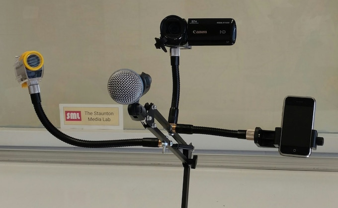 The ARMi Assistive Technology Arm shown with four devices attached: Action Camera, Microphone, HDcam, and smartphone. Devices not included.