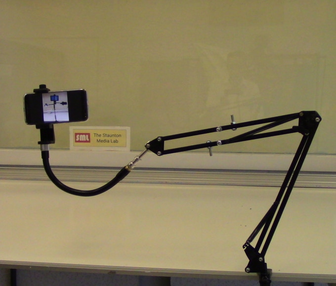 The ARMi Assistive Technology Arm shown with extra-long gooseneck, a fancy smartphone holder and a smartphone. Smartphone not included.