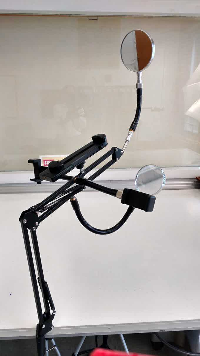 The ARMi Assistive Technology Arm with one additional arm. Mirror (top), magnifying glass (bottom), smartphone clamp (right), fancy smartphone holder (left) and tablet holder on ARMi's back!