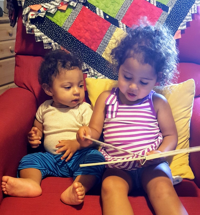 """Sophia """"reading"""" to Judah, one of our favorite family pastimes."""
