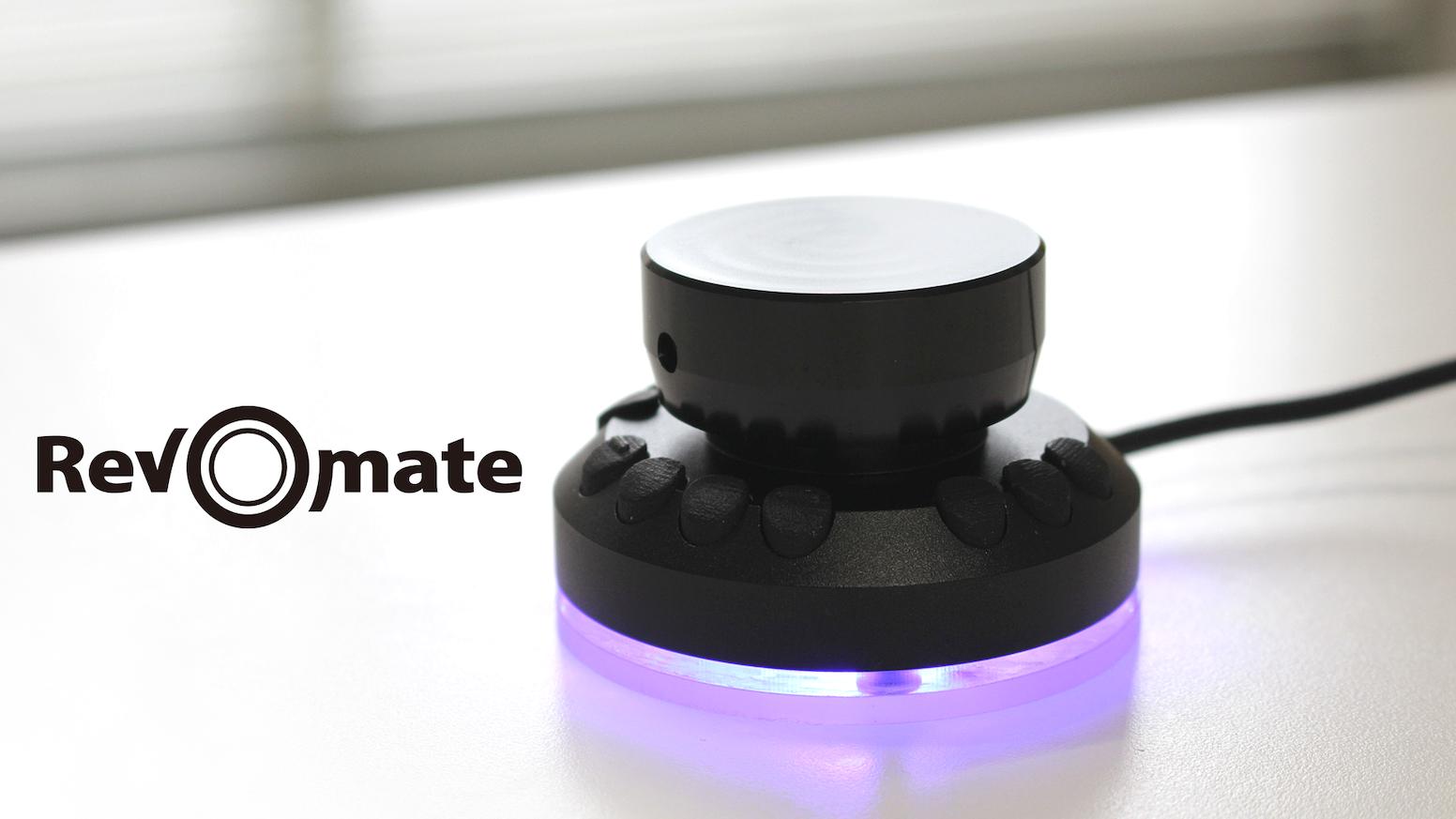 """""""Rev-O-mate""""は無限回転ダイアルと柔軟に設定可能な10個のボタンを備えたクリエイター向けデバイス。 異なるアプリ間での拡大縮小・回転など設定は思うまま。 アルミダイキャストの頑強なボディはLEDに彩られ、高級感溢れる佇まいで貴方のデスクを飾ります。"""