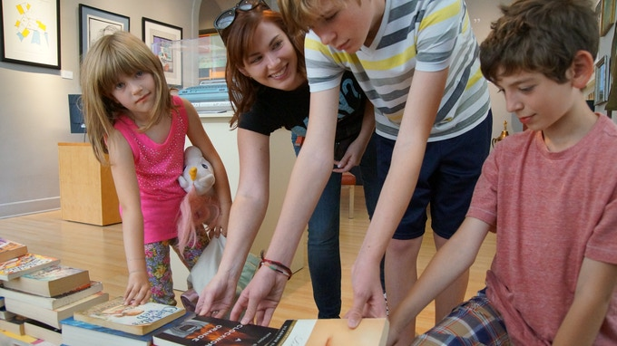 Young visitors help build the Banned Books Week prison wall