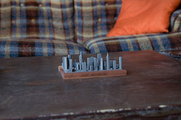 Perspective shot of the LA skyline to get a feel for size in real life. It is sitting on a large coffee table in front of a plaid couch.