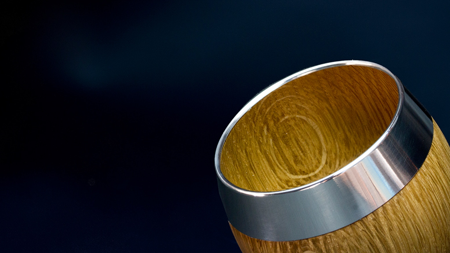 A beautiful handmade whisky tumbler with a one-piece oak body and stainless steel top, an exquisite drinking experience.