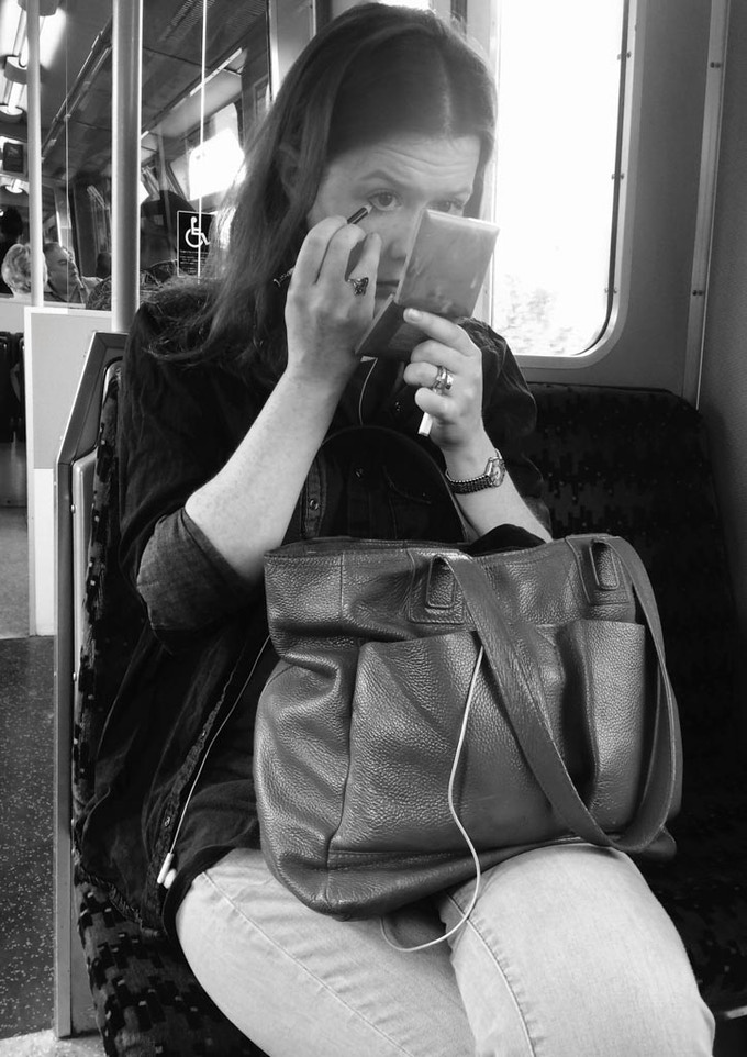 Woman does her makeup on the train