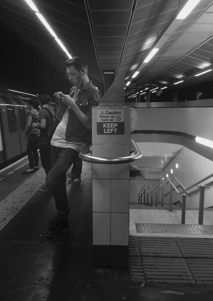 A man checks his phone on the platform