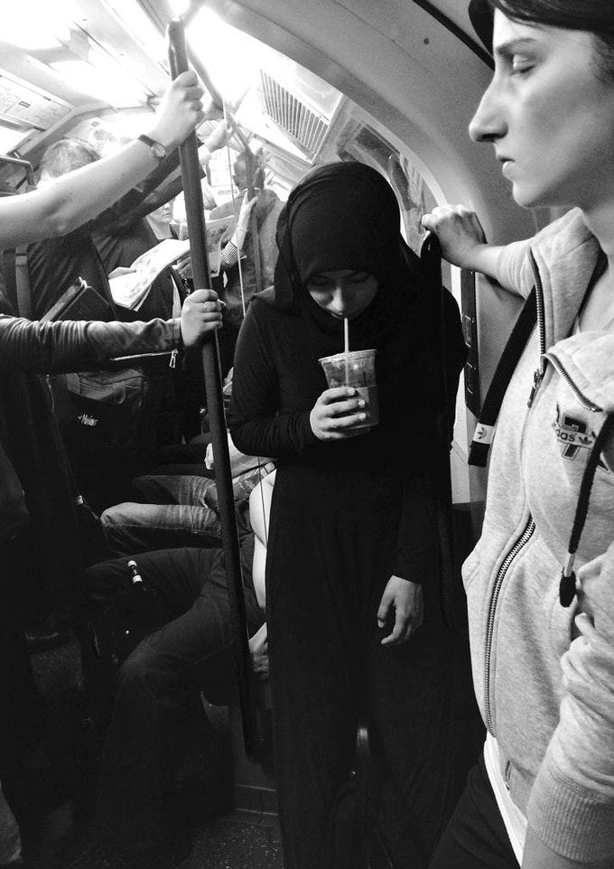 Young woman having a smoothie on a busy train