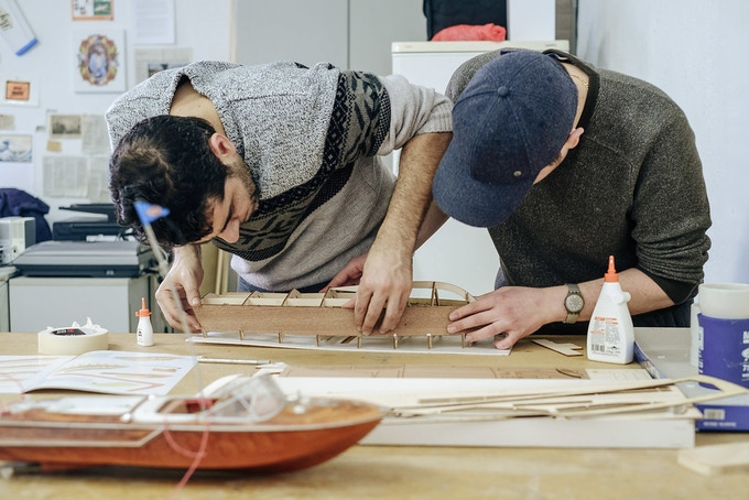 Hassan Aji and Alain Alwali construct a scale model of an Overnight Cruiser.